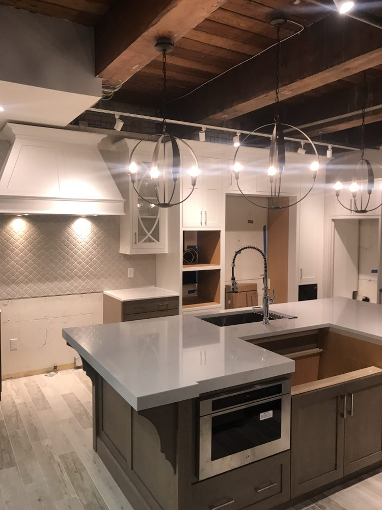 Appliance and circular pendant light installations about kitchen island