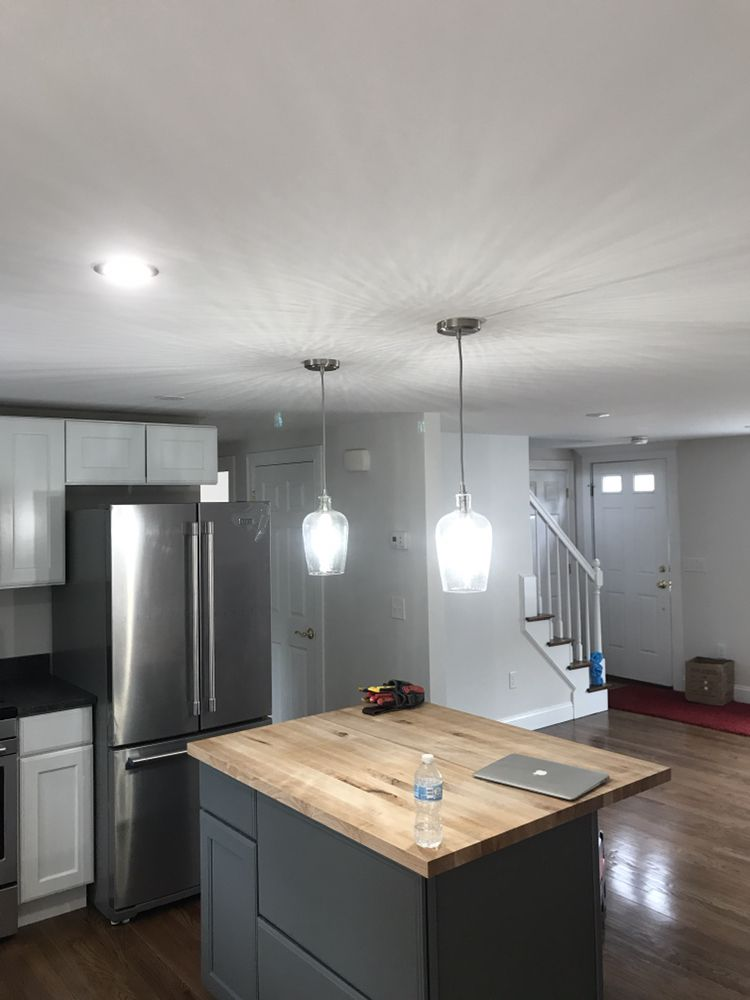 Glass pendant lights installed above kitchen island wood block